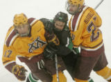 North Dakota's Ryan Duncan gets caught in the middle of Minnesota's Blake Wheeler, left, and Jay...