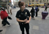 Denver police officer Colleen O'Dell, takes a call on her radio to do a body search on a suspected...