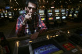Jason Shorey, (cq), takes a drag off his cigarette while he plays Double Bonus Poker tabletop at...