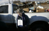 Carol Gilbert, O.P. rests against a truck filled with donated food outside of Buckley Air Force...