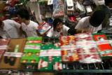 (DLM1351) -  Teacher Joyce Cole, center, pushes shoe boxes filled with Christmas gifts bound for...