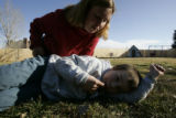 Jean Illig hugs her son, 8 year old Fletcher Illig in the backyard of their  family's home...