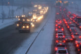 Early morning motorist at Thornton Parkway and northbound I-25, line up behind CDOT snow plows and...
