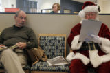 Santa fills out paperwork before giving blood at the Bonfils Blood Center's Lowry Community Donor...