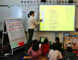 Third grade teacher Lisa Newell (cq) uses an interactive white board during class Thursday morning...