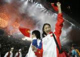 AGCER124 - Chinese athletes reacts as they gather in the center of the arena as fireworks erupt...