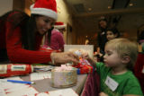 Volunteer Cynthia Veach, cq, places a bow on a gift that Josiah Speer, 4, of Longmont picked for a...