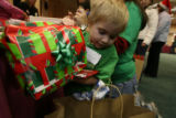 Josiah Speer, 4, of Longmont places a gift that he had wrapped for his dad in his shopping bag at...