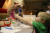 Volunteer Cynthia Veach, cq, (left) hands Josiah Speer, 4, of Longmont his gift after she wrapped...