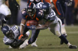 Tatum Bell is tackled by ken Hamlin and Jordan Babineaux in the second quarter of the Denver...