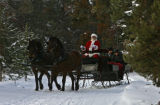 Santa Claus (Dale White (cq)), left, drives a team of horses while giving a sleigh ride to a...
