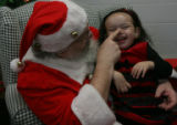 Santa finds Miranda Soto's nose, 2, (cq), and makes her laugh and smile. She was a little timid in...