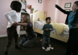 Stapleton resident Kelly Anolin helps her daughter Grace, 6, get dressed while her son, Lincoln,...