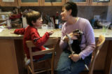 Mandy Koskinen helps her son Jack, 8, with his homework while she tries to hold their beagle puppy...