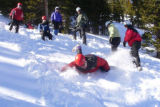 A Wilderness Trekking School student practices self-arrest on the snow travel field day.