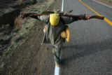 Aaron Lovato (cq) walks, carrying his walking stick like a cross, to the Chimayo Sanctuary, on...