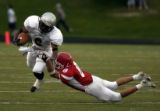 (AURORA, Colo., SEPTEMBER 3, 2004) Regis High School's Parker Heaston tackles Montbello's Enoch...