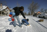 Jennifer Draper Carson tries to keep a grip on Henry while he pushes his car on their snowy...