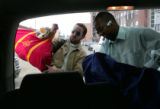 Nur Negawo (cq) right, a Denver area taxi driver, unloads a businessman (OK with photo didn't want...