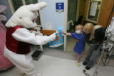 Kelcee Braden, 4, was tentative but then eager when Bunny offered a gift bag as she is safely held...