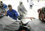 BG0381 Air Force goalie coach Grady Hunt, second from left, keeps the players in good spirits...