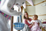 DLM6307  Eight-month-old Alex Thisted gets a visit from the Easter Bunny as she sits on the lap of...