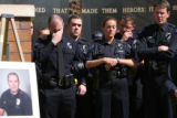 Aurora Police officer Justin Grizzle, cq, (far left) reacts to the death of best friend and fellow...