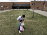Demetri Hernandez tries to get his sister, Santina Duran, 4, to go into DPS' Henry Middle School...