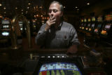 Paul Stone, (cq), smokes while he plays Double Bonus Poker tabletop at the bar of the Doc Holiday...