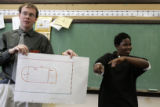 Smiley Middle School student math teacher Donovan Hill (cq)(l) holds up a connected math problem...