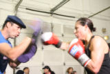 Vanessa Espinoza's (cq), right, trains with boxing coach Antonio Barela, left, while Vanessa...