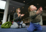 Sarah Schwartz (cq), and her son Eli Schwartz (cq), 10 months, both of Denver, applaud at a...
