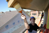 Aurora Police recruit officer, Jeremy Jenkins paints the exterior of a Habitat for Humanity Home...