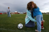 DLM0981  Laura Reed puts shin guards on 4-year-old daughter, Jessica Reed, before her soccer...