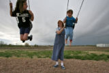 DLM0348  Laura Reed pushes her daughters Sarah, 8, left, and Jessica, 4,  as they swing on the...