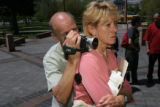Anthony Satriano, (cq), uses his wife Jan as a tripod to video his cousin Tom Satriano speaking...