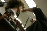 0382 Sonia Luna, CQ, 33, mother of three, works with a mannequin as she attends cosmetology class...
