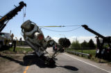 A cement truck is pulled upright by two heavy duty tow trucks  after  after tipping over on the...