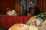Kahlil Essebar, 5 months, sit in a cradles near his father Hassan Essebar and mother Amal Darif,...