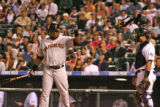 Giants Barry Bonds throws his elbow protector over Rockies catcher, Yorvit Torrealba, after being...