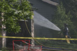 A Thornton firefighter sprays water on a housefire which occured at 12222 Forest Way in Thornton,...