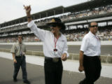 NAA113 - Seven-time NASCAR series champion Richard Petty waves as he walks along pit road before...