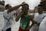 Winner of the Men's Elite race Ridouane Harroufi is showers by his cousin Youssef Ennaciri (cq)...