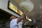Khalifa Eltarhuni (cq) who has worked here for 10 years, tosses pizza dough at Famous Pizza as we...
