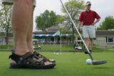 "(from left) Steve Ritter (cq) putts his ball in front of The ""Tin Cup Bar and Grill"" in..."