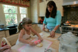 Hannah Butler, 3 is able to help her mom Erin Butler with rolling out the dough for empanadas with...