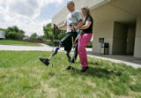 Tyler Carron (cq),left,  walks with the help of his physical therapist Sylvia Boedeker (cq),...