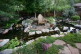 A koi pond and a series of subtle waterfalls surround a solitary rocking chair in one of the...
