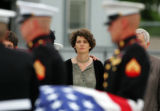 Step-mother Maggie Walsh, center, watches as the casket of U.S. Recon Marine Sgt. Nicholas Walsh,...