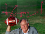 Jack Neumeier, retired high school football coach at Granada Hills H.S., poses next to one of his...